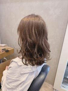 優しい髪色のパーマの女性