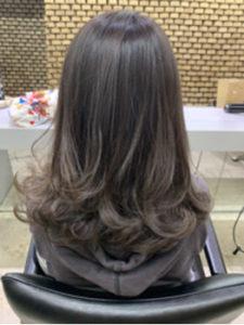 毛先に細く明るい色が入った暗髪のロングヘアーの女性