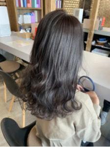 暗髪パーマのロングヘアの女性