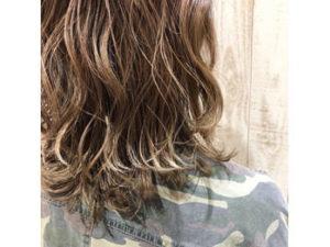 細く明るい髪色の入ったボブパーマの女性